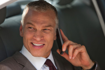 Businessman talking on cell phone in back seat of car