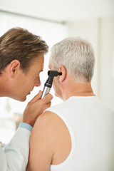 Doctor examining patient's ear in doctor's office