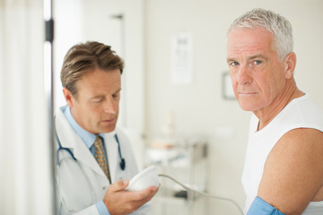 Doctor taking patient's blood pressure in doctor's office