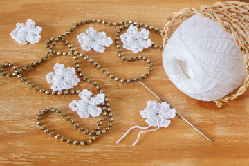 White crochet snowflakes for Christmas decoration on wooden tabl