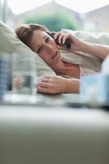 Sick woman laying on sofa talking on telephone