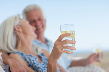 Senior couple drinking water on beach