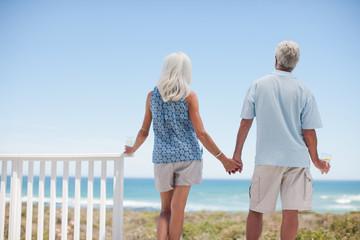 Senior couple holding hands on beach patio