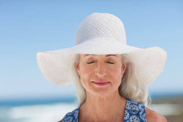 Close up of woman closing eyes with wearing sun hat