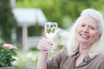 Senior woman drinking wine at patio table