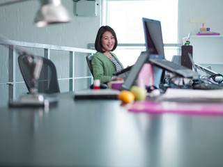 Businesswoman writing on note pad in office