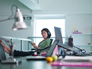 Businesswoman with headphones writing on note pad in office