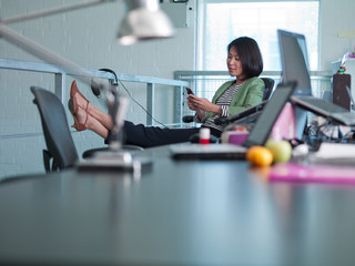 Businesswoman using cell phone with feet up in office