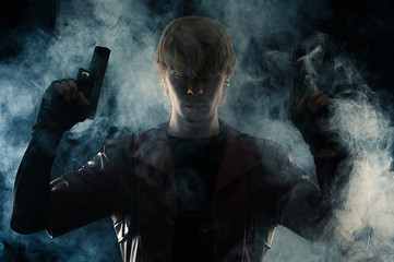 artportrait man with two pistols in hands in the smoke