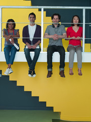 Men and women sitting in a row on ledge