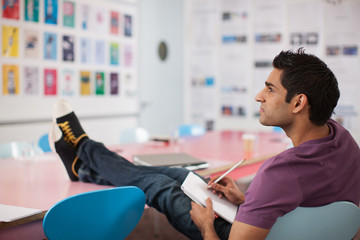 Man writing on notepad with feet up in office