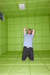 Man pulling at hair and screaming in padded room