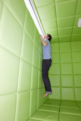 Man reaching to look out window in padded room
