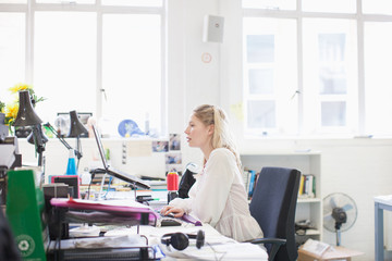 Businesswoman working on laptop at desk in office