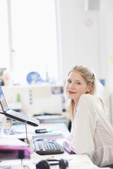Smiling businesswoman working on laptop at desk in office