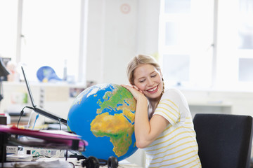 Smiling businesswoman leaning on globe at desk in office