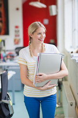 Smiling woman  holding laptop and paperwork in office