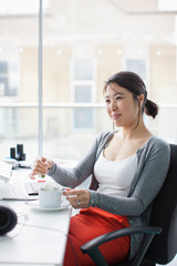 Smiling businesswoman  in office with coffee