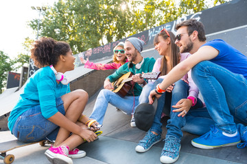 Young people playing guitar at the skatepark