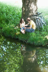 Couple with bicycles sitting on riverbank together