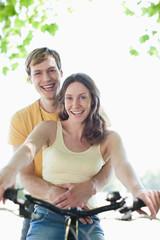 Smiling woman riding boyfriend on bicycle