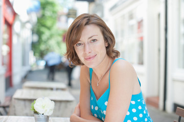 Smiling woman sitting at cafe table