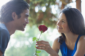 Smiling couple outdoors with red rose