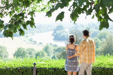 Couple hugging outdoors looking at landscape