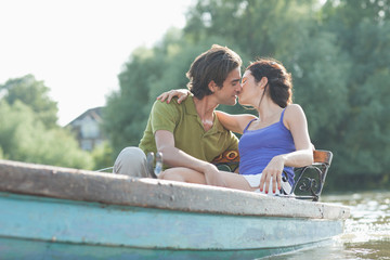 Couple kissing in rowboat on lake