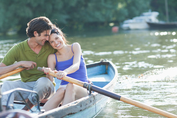 Couple rowing rowboat together on lake