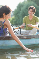 Man rowing girlfriend in rowboat on lake
