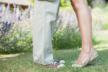 Woman standing on tip toe with boyfriend in park