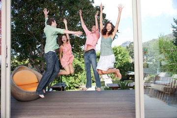 Friends jumping around on a deck