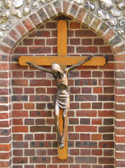 A Wooden Cross with Jesus in a Brick Wall Alcove.