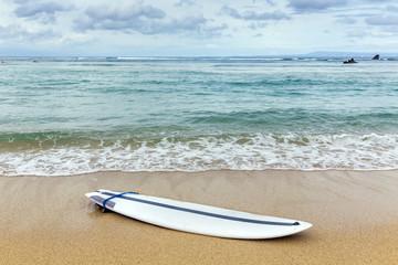 Surfboard lying on sand near the ocean