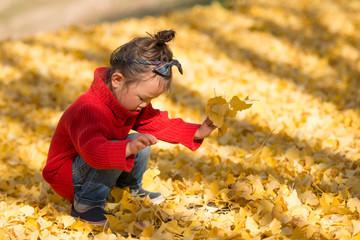 銀杏の葉で遊ぶ少女