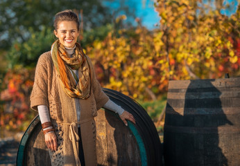 Portrait of happy young woman standing near wooden barrel