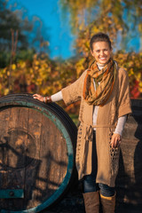 Full length portrait of happy young woman near wooden barrel