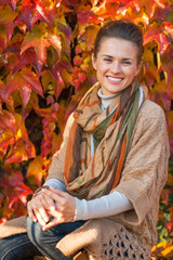 Portrait of smiling young woman in front of autumn foliage
