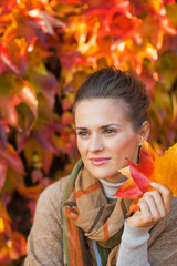 Portrait of thoughtful young woman with autumn leafs