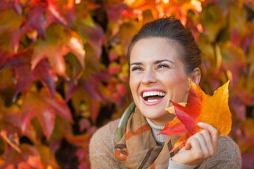 Portrait of smiling young woman with autumn leafs