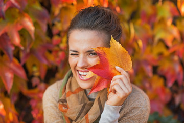 Portrait of happy young woman hiding behind autumn leafs