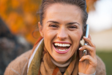 Portrait of smiling young woman in autumn outdoors in evening