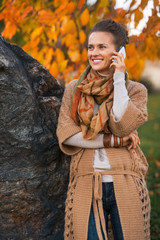 Smiling young woman talking cell phone in autumn outdoors