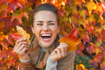 Portrait of happy young woman with leafs in front of foliage