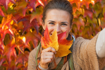 Happy young woman hiding behind leaf while making selfie