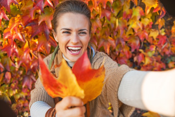 Smiling young woman with autumn leaf making selfie