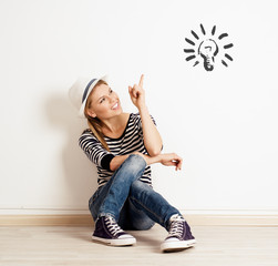 Young smiling woman pointing at light bulb drawn at the wall