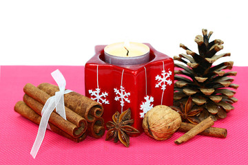 Candle, cinnamon, nuts, and conifer