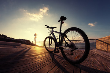 silhouette of  sportsman and mountain bike at the sunset